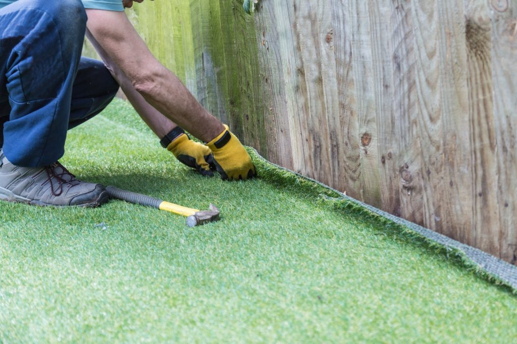 man installing artificial turf