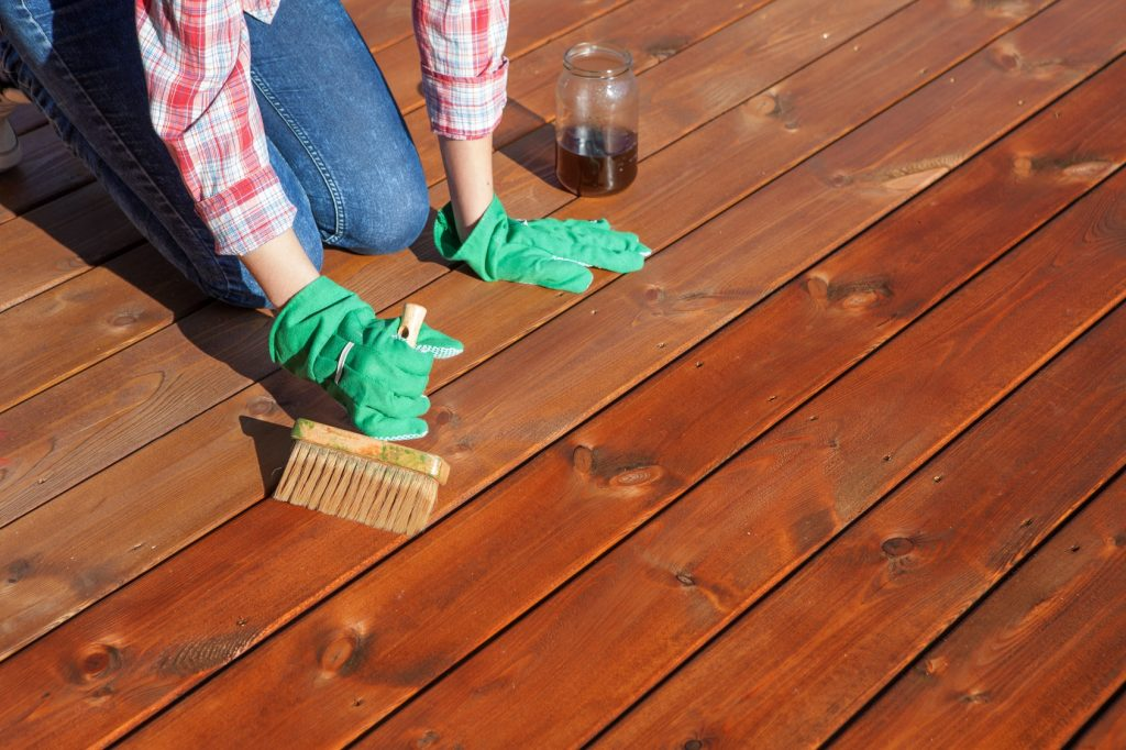 lady staining wooden decking